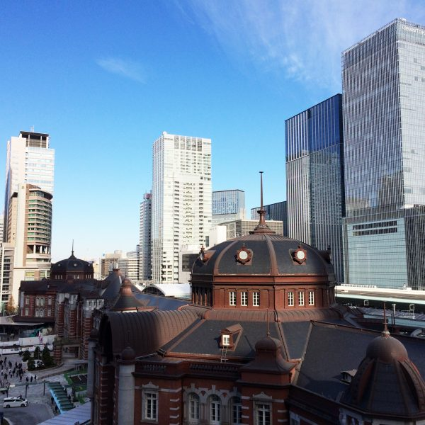 JPタワーから眺めた東京駅丸の内駅舎と高層ビル街の写真