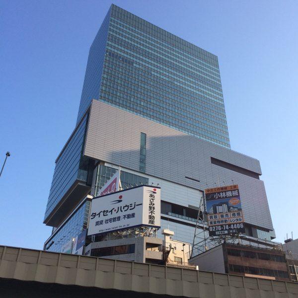 渋谷ヒカリエと雑居ビルの看板・首都高の高架の写真